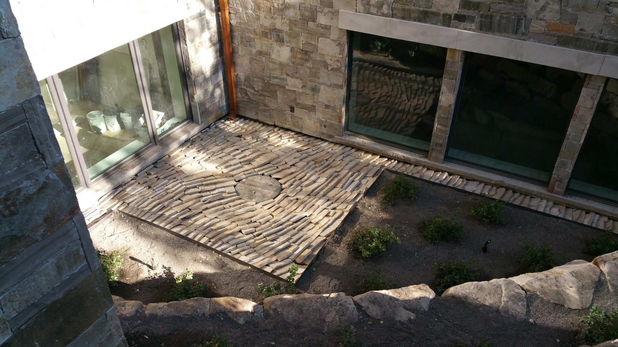 Laid stone mulch surrounding sculpture base in light well